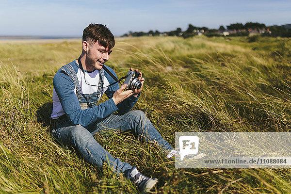 Lächelnder junger Mann sitzt auf einer Wiese und schaut in die Kamera.