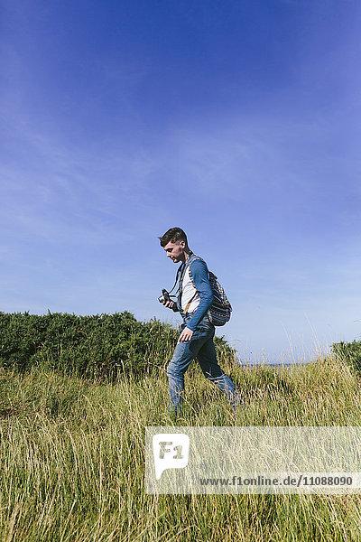 Junger Mann mit Kamera in der Natur unterwegs