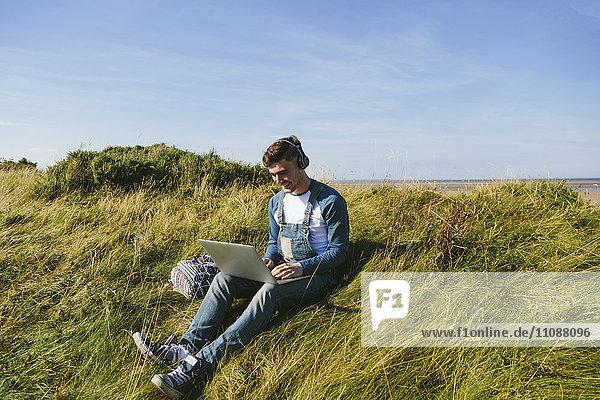 Entspannter junger Mann mit Kopfhörer auf einer Düne sitzend mit Laptop