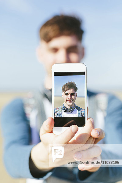 Selfie des lächelnden jungen Mannes auf dem Display des Smartphones