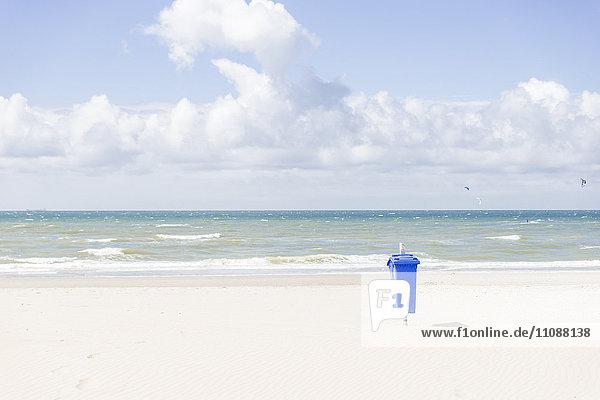 Leerer Strand mit blauem Mülleimer