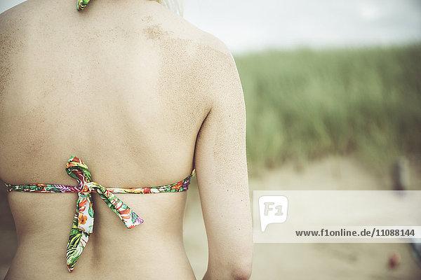 Rückseite der Frau am Strand  Teilansicht