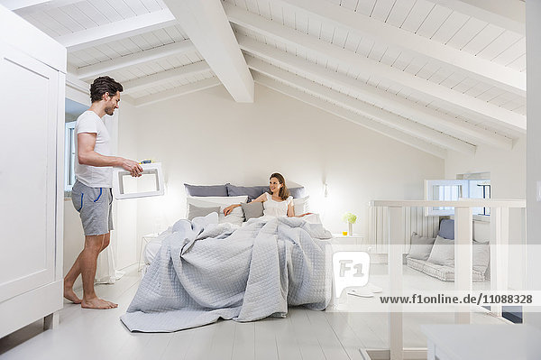 Mann bringt Tablett mit Frühstück ins Bett