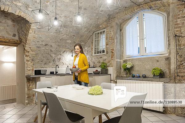 Frau in der Küche bereitet Obstsalat zu