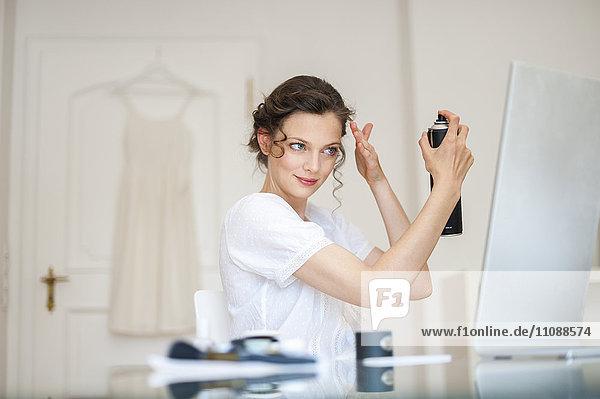 Frau zu Hause beim Frisieren mit Haarspray