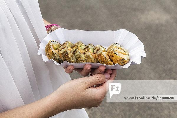 Hände des Teenagermädchens halten Schale Sushi mit Garnelen