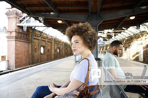 Junge Frau sitzt auf der Bank am Bahnhof