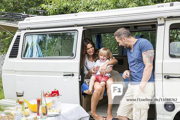 Glückliche Familie mit Van in der Natur