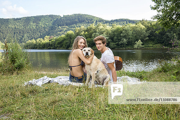 Junges Paar mit Hund sitzt am Seeufer