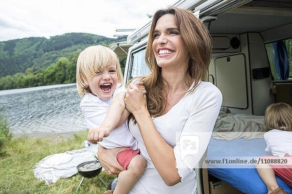 Glückliche Mutter mit Kleinkind im Van am Seeufer
