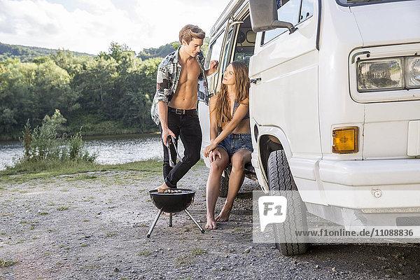 Junges Paar beim Grillen im Transporter