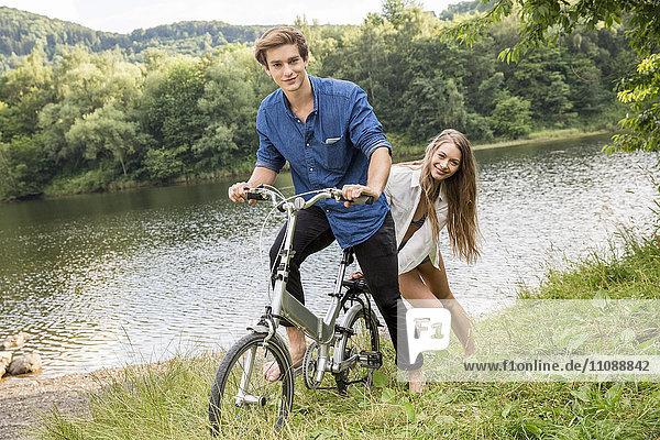 Junges Paar mit Fahrrad am Seeufer