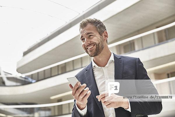Lächelnder Geschäftsmann im Bürogebäude mit Handy