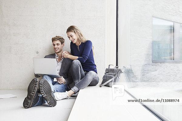 Lächelndes junges Paar sitzt an der Betonwand und teilt sich den Laptop.