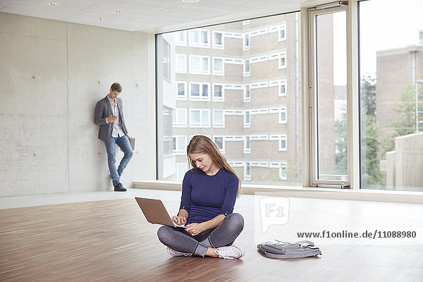 Junge Frau mit Laptop in leerem Raum mit Mann im Hintergrund