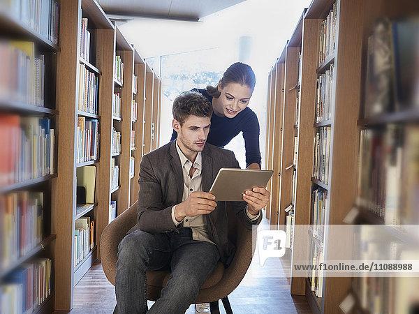 Junger Mann und Frau mit Tablette in der Bibliothek