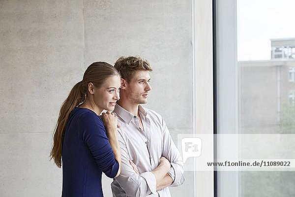 Young couple looking out of window