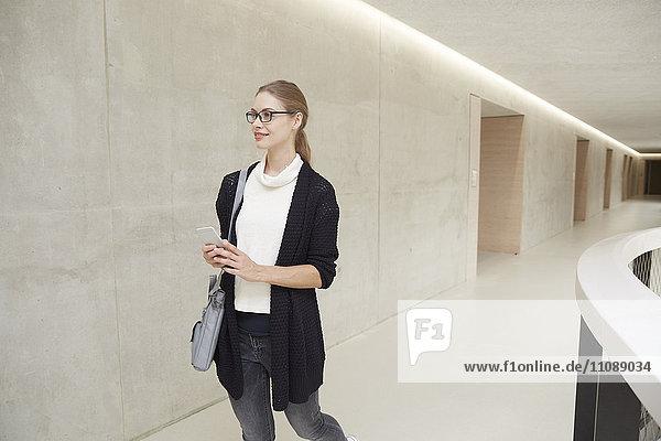 Lächelnde junge Frau  die auf dem Flur des Gebäudes geht