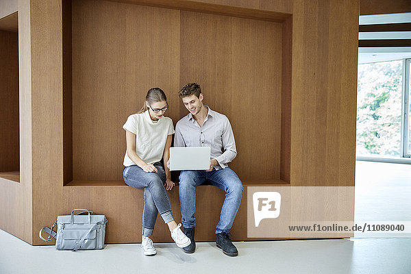 Young man and woman sitting on wooden ledge using laptop