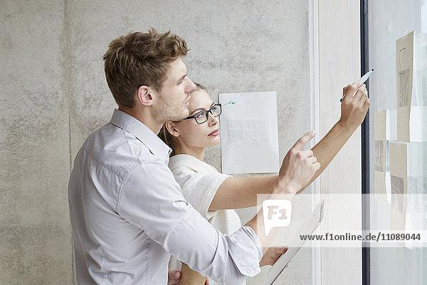 Junger Mann und Frau bei der Arbeit an der Glasscheibe