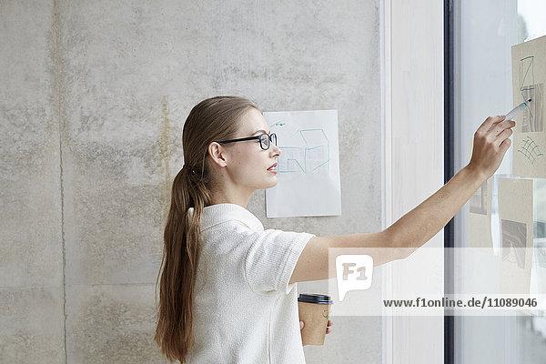 Junge Frau schaut auf Zugluft auf Glasscheibe