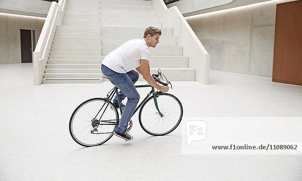 Junger Mann auf dem Fahrrad im Foyer