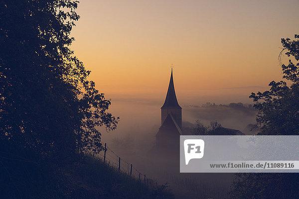 Deutschland  Weinsberg  Kirche bei Sonnenaufgang  Nebel