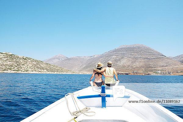 Griechenland  Rückansicht eines Paares  das Arm in Arm am Bug eines Bootes sitzt und auf die Insel Amorgos schaut.