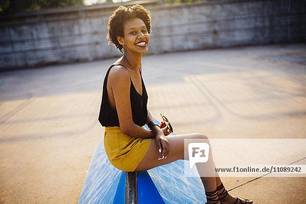 Lächelnde junge Frau sitzt im Skatepark bei Gegenlicht