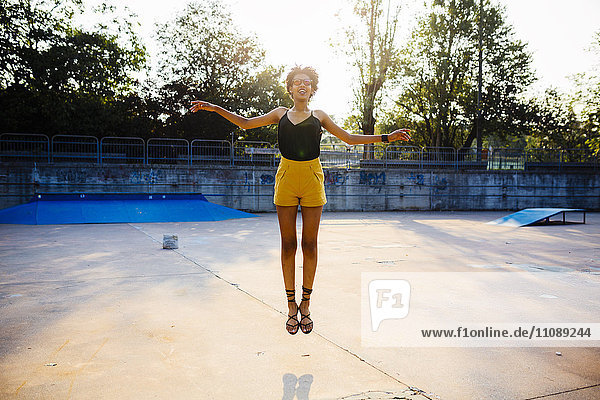 Young woman jumping in the air in a skatepark