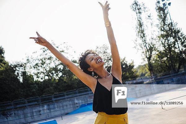 Glückliche junge Frau im Skatepark mit Siegeszeichen