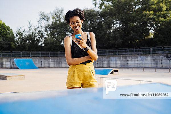 Lächelnde junge Frau im Skatepark mit Blick auf das Handy