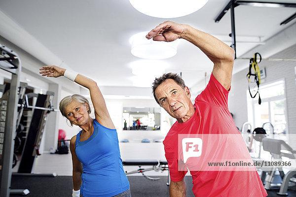 Reife Frau und älterer Mann beim Turnen im Fitnessstudio