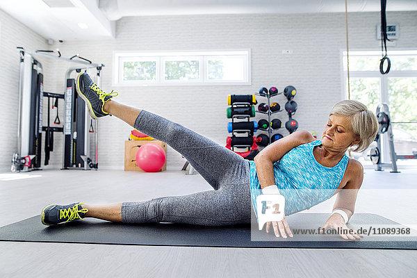 Reife Frau beim Turnen im Fitnessstudio