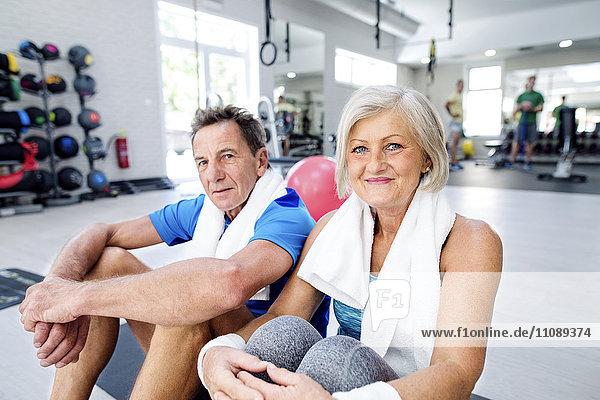 Porträt der lächelnden reifen Frau und des älteren Mannes im Fitnessstudio