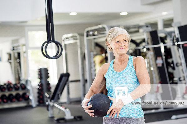 Reife Frau mit Ball im Fitnessstudio