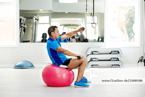 Senior Mann beim Training mit Hanteln auf dem Fitnessball im Fitnessstudio