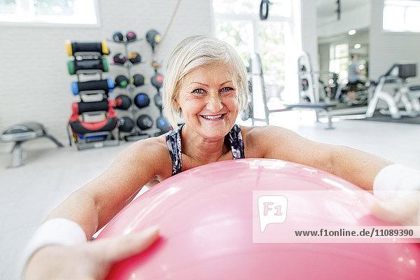 Porträt einer lächelnden reifen Frau mit Fitnessball in der Turnhalle