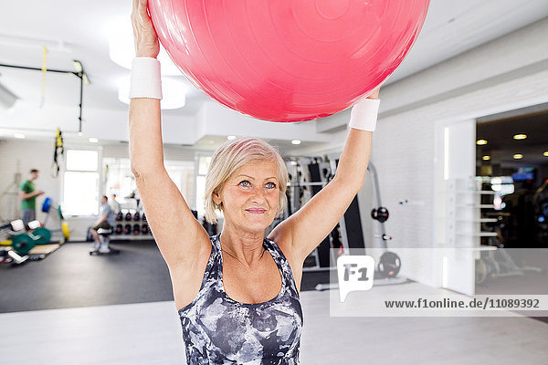 Reife Frau beim Anheben des Fitnessballs im Fitnessstudio