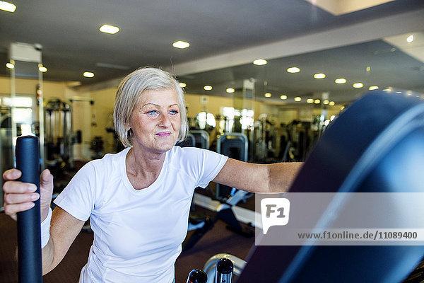 Reife Frau beim Training auf dem Stepper im Fitnessstudio