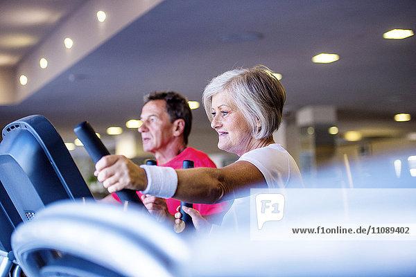 Senior-Mann und reife Frau auf Step-Maschine im Fitness-Studio