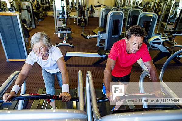 Senior Mann und reife Frau beim Training auf dem Laufband im Fitnessstudio