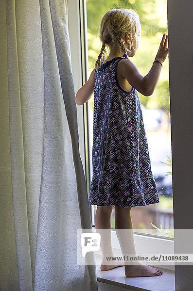 Kleines Mädchen steht auf der Fensterbank und schaut durchs Fenster.