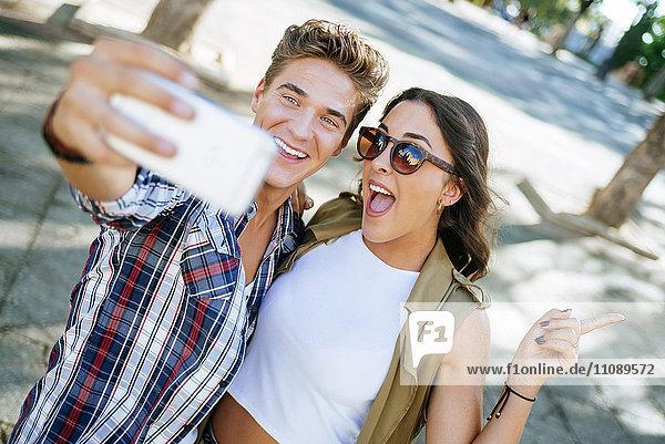 Junges Pärchen nimmt Selfie mit Smartphone