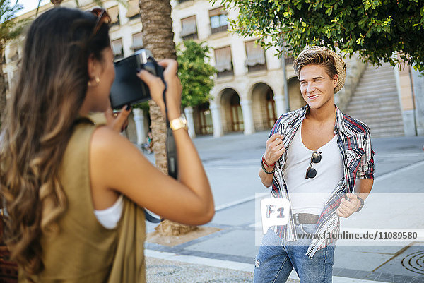 Young woman taking a picture of her boyfriend