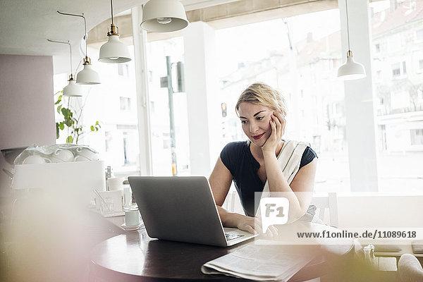 Frau mit Laptop in einem Café