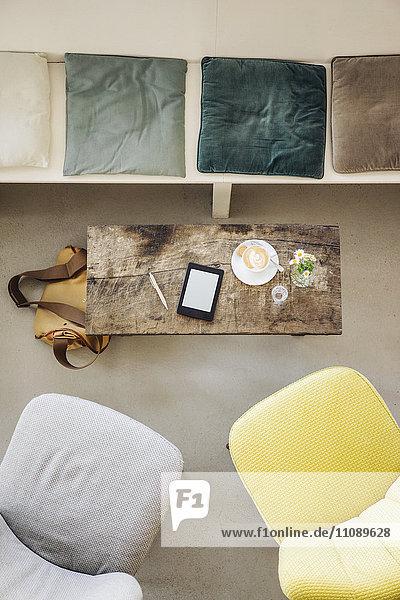 E-Book und Tasse Kaffee auf dem Tisch im Cafe