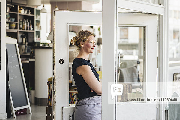 Lächelnde Frau in einem Café mit Blick aus dem Fenster