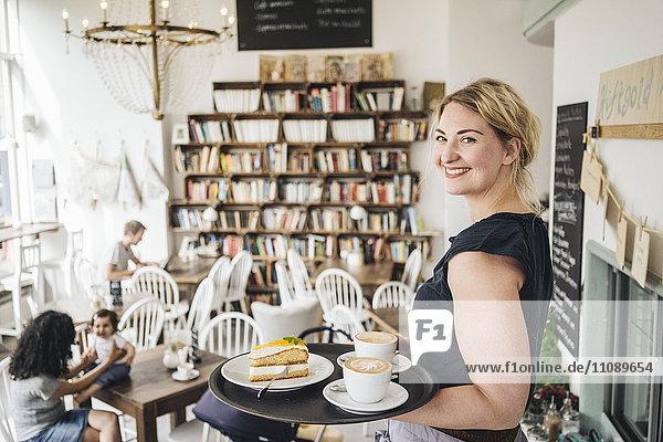 Lächelnde Kellnerin im Café mit Kuchen und Kaffee