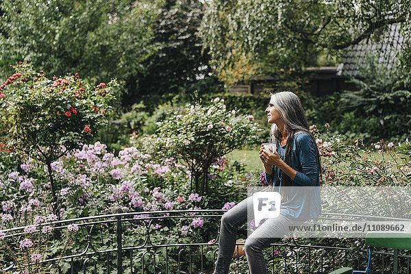Frau mit Kaffeetasse auf Balkongeländer sitzend mit Blick in die Ferne